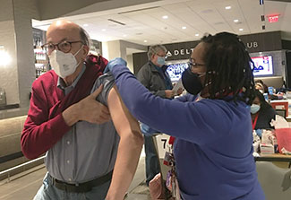 Fogarty Director Dr. Roger Glass receives a covid vaccine from a healthcare worker at a vaccine clinic.