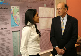 Woman speaks with Dr Roger I Glass in front of large poster displayed in conference room
