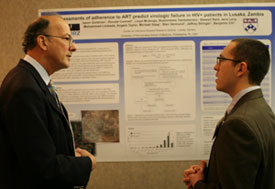 Dr Roger I Glass speaks with man in front of poster pinned to large bulletin board, displayed in conference room