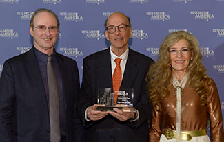 Tom Hutton and Mara Hutton of the Geoffrey Beene Foundation pose with Roger Glass, who holds his award
