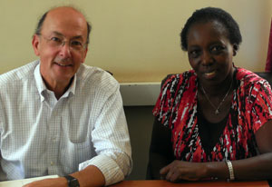 Dr Roger I Glass and Dr Harriet Mayanja-Kizza seated next to each other, both looking at camera