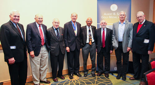 Eight men, all previous Sabin gold medal winners, pose in a row for the camera, with Roger Glass in the middle