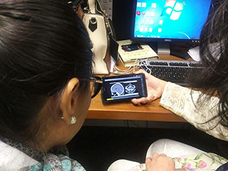 Two researchers seated with backs to camera in front of a computer view a video of brain scans on a mobile device