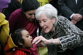 Kathleen Sebelius administers polio vaccine to young child, woman looks on closely from behind