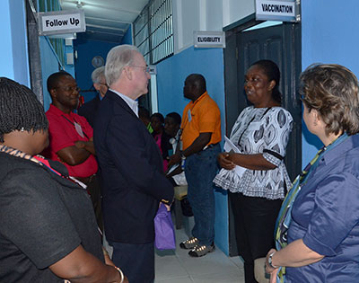 Secretary Tom Price stands in a hallway listening to a woman who speaks to him in a clinic in Liberia
