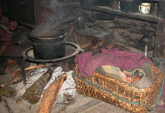 Small baby wrapped in blankets in small basket on floor of a dark hut, very close to smoking wood burning fire