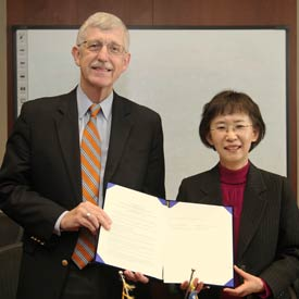 NIH Director Dr Francis S Collins and Korean official Dr Kyung-Hwa Ko hold up document for camera