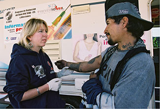 Woman wearing plastic gloves holds the arm (with many tatoos) of a man in front of a mobile health clinic.