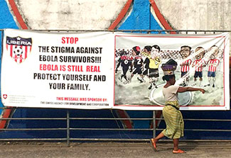 Woman walking in street in Monrovia, Liberia, in front of large football banner reading: stop the stigma against Ebola survivors
