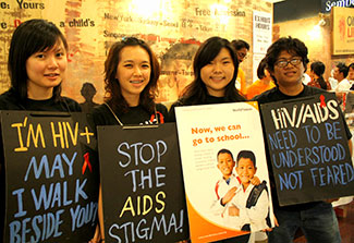 Four volunteers in Malaysia wear signboards reading: Stop the AIDS stigma!