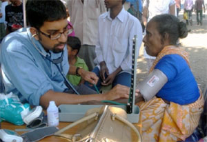A male medical worker with stethoscope takes the blood pressure of an older woman, seated, in an outdoor clinic