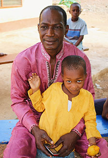 Man sits with his son outdoors in Ghana
