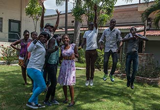 Group of teenagers in outdoor courtyard in Haiti pose for camera, some jump and raise hands.