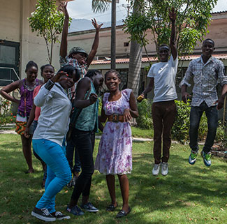 Group of teenagers in outdoor courtyard in Haiti pose for camera, some jump and raise hands