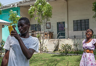 Teenage boy takes a selfie with cellphone camera with teenage girl in the background, in outdoor courtyard in Haiti