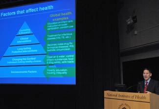 CDC Director Dr. Thomas R. Frieden speaks, slide projected to his left