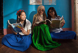 Three teenage girls seated on floor read from lesson books