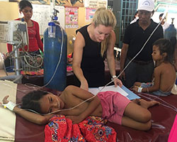 Dr. Jessica Manning works with a child patient in a clinic setting in Cambodia while others look on.