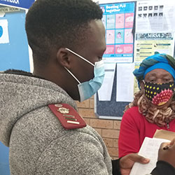 Researcher wearing a mask takes notes on a clipboard while interviewing a masked subject in a clinic.