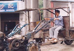 Chinese man sits on parked tractor