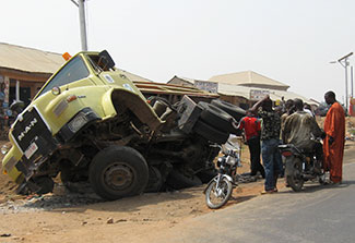 On the side of the road, a badly damaged large truck lays on its side, people gather to inspect the accident.
