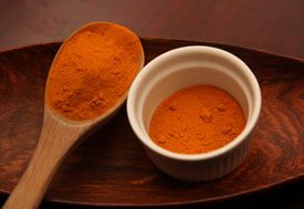 Close up of turmeric, an orange powder, in a small dish with a large wooden mixing spoon