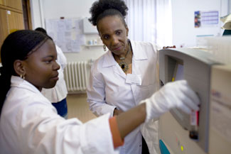 Two female researchers working in a lab, younger one works with equipment, older one by her side observes