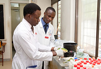 Two researchers in lab coats work in a lab preparing materials