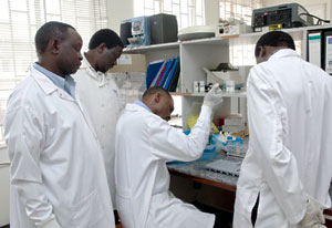 Group of researchers in lab coats, one seated inserts samples into vials, three others observe