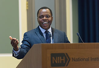 Dr. Jean Utumatwishima speaks from an NIH podium in a conference room