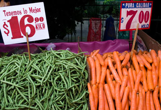 Large piles of green beans and carrots on display at outdoor market with signs showing prices