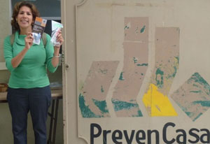 Dr. Victoria Ojeda stands holding brochures next to a sign for the PrevenCasa clinic