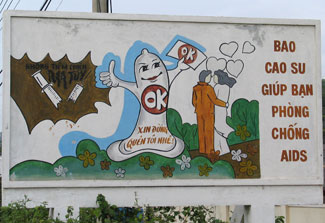 "Cartoon outdoor billboard in Vietnam shows broken syringe, large condom reading ""OK,"" and a couple surrounded by hearts"