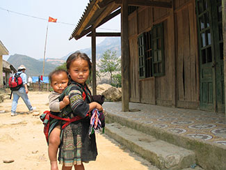 Young Vietnamese girl with boy toddler strapped to her back, standing in front of wooden house on dry dirt ground