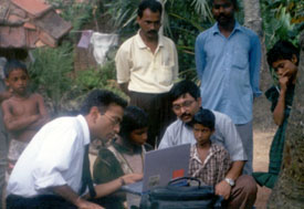 Outdoors, child seated at laptop is instructed by man in shirt and tie, adult and another child look on close by, more men and c