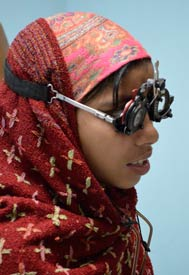 Young girl wearing head scarf wears large eye exam glasses over head to test vision with different lenses