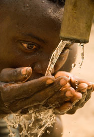 Close up of person with cupped hands drinking water flowing from a pipe
