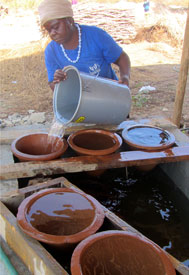 A woman pours water into a household water container with a clay water filter