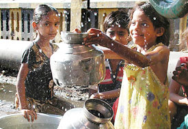 Three young girls gather by water pump, one holds up large metal jug, drops of water splashing