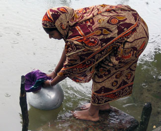Woman dressed in sari stands on rock at edge of water, dips urn with sari cloth covering opening into water to filter it