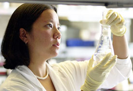 Female researcher in lab holds up and observes contents of a flask