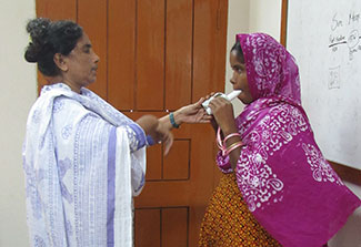 Health worker administers a test of lunch function to a woman using a spirometer.
