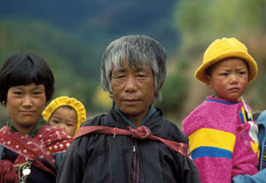 In Bhutan, one older woman and one younger woman with young child strapped to back, another young child held on hip by person of