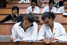 Female students in white lab coats seated in lecture hall take notes