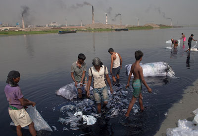 Many Men Wading In River Bank Rinsing Large Clumps Of Plastic Bags Smoking Factories