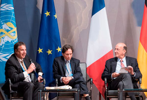 Roger Glass seated on a stage during the World Health Summit with two other men, multiple flags in the background