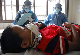 Young boy lies in hospital bed, holds protective mask to face, nurses observe in background