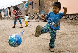 A young boy plays soccer in the neighborhood street in Peru
