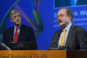 Sir Mark Walport speaks at a podium, NIH Director Francis S Collins looks on