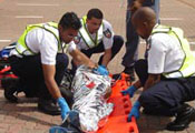 Three male emergency response workers in uniforms carefully roll wrapped, adult-sized body from brick pavement onto stretcher